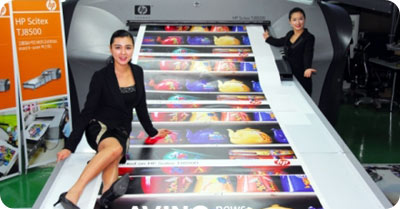 Chicas de HP mostrando una impresora gigante
