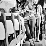 Sobrecargo con botas y minifalda conversando con viajero