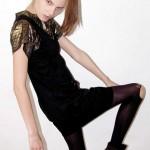 Modelo con vestido negro y medias rotas oscuras