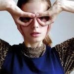 Una modelo haciendo de heroina con las manos, vestida vintage