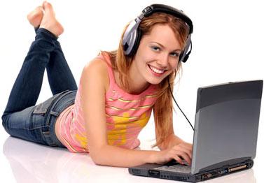 chica con laptop y audifonos, acostada y sonriente