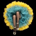 piernas de mujer con medias negras y falda azul con amarillo