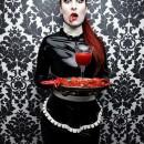camarera gotica de negro, sirviendo con rostro expresivo