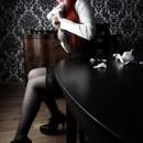 Chica gotica con medias negras mordiendo papeles